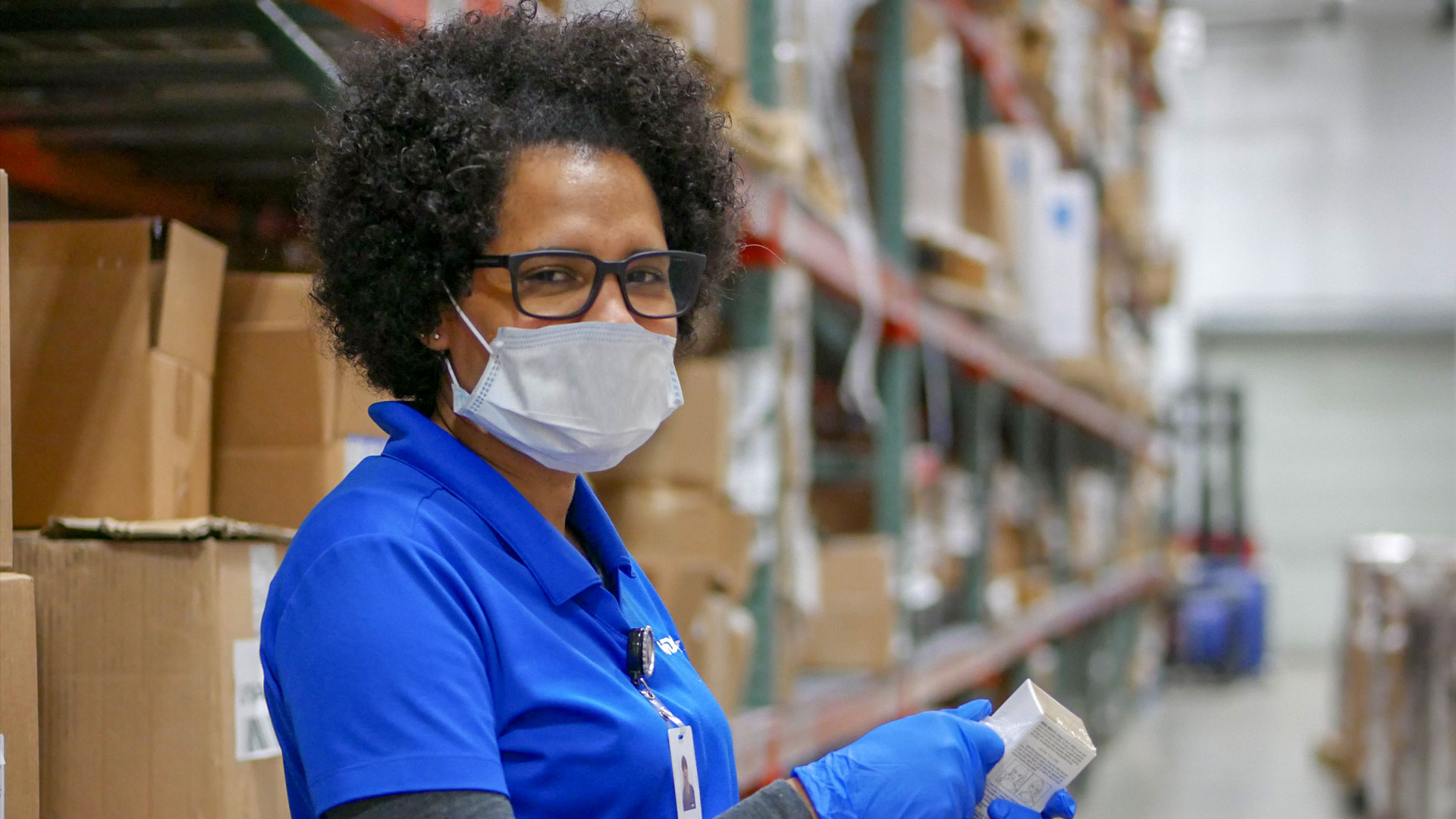 Warehouse Technician wearing PPE at the Pharmaceutical Logistics warehouse as required by policies