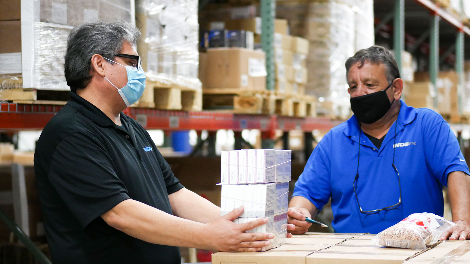 Employees at a Pharmaceutical Logistics Industry pick orders to supply a client's demand.