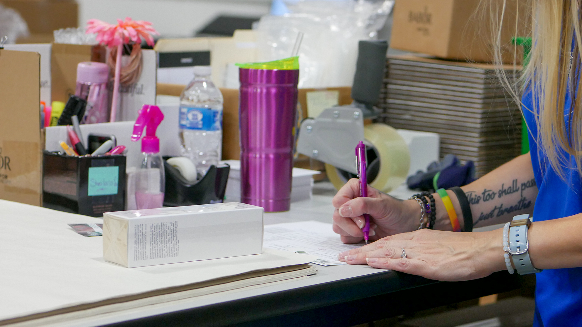 WDSrx Warehouse Technician writes a handwritten note that will be put in the customer's package.
