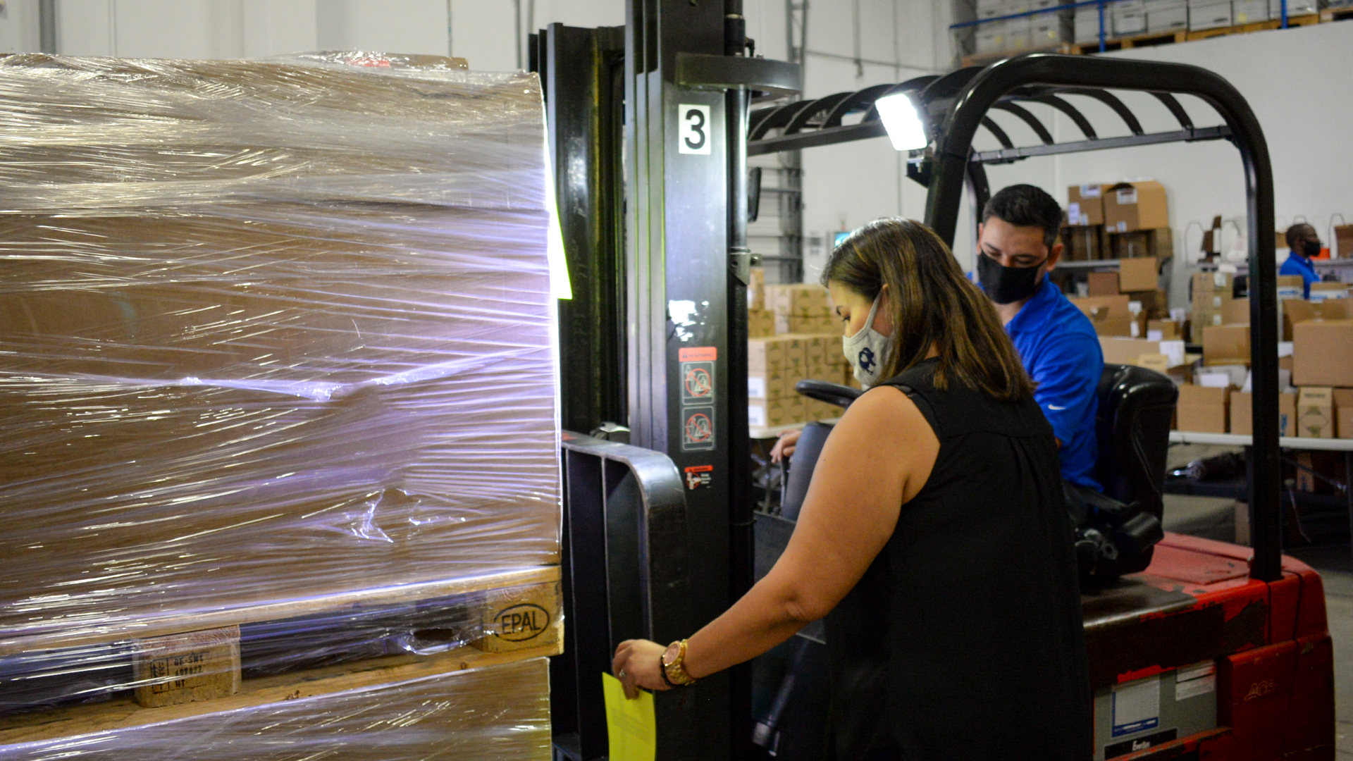 Reverse Logistics Manager places proper documentation on pallet for regulatory compliance while Warehouse Technician waits to load product onto truck with a forklift.