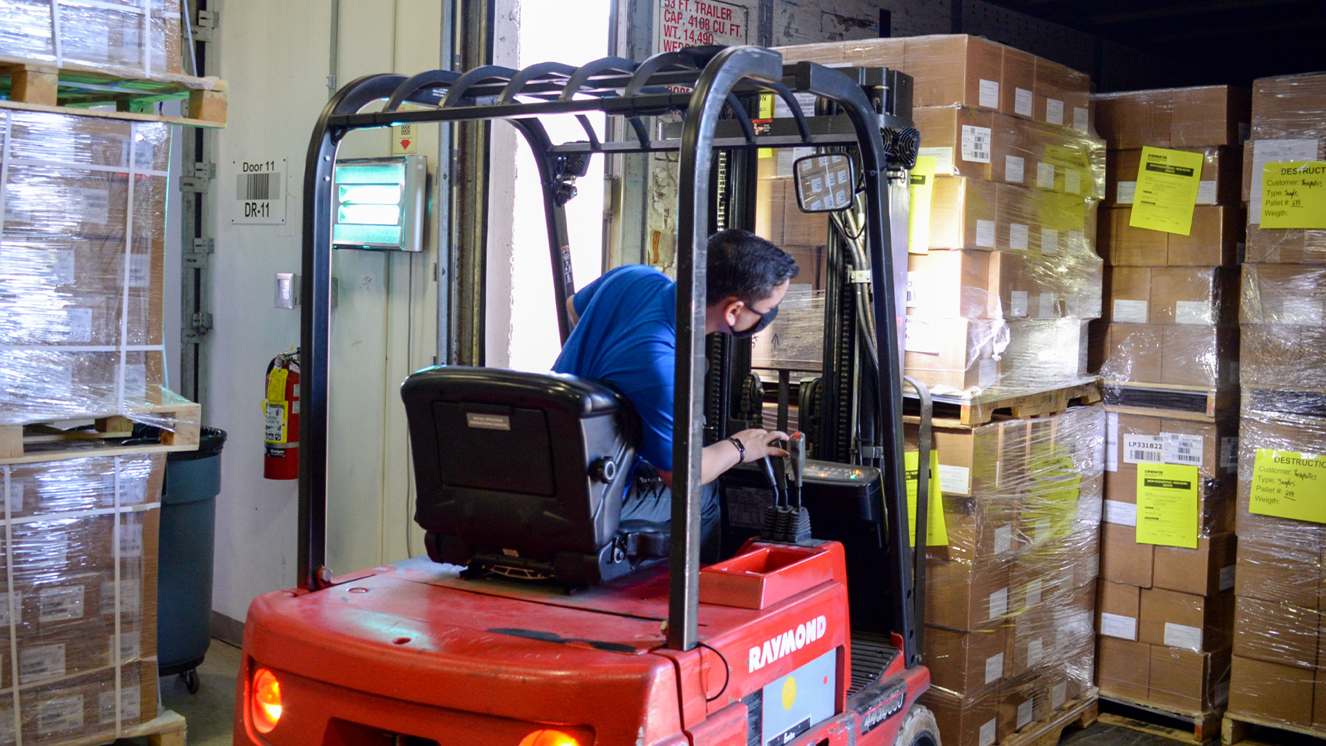 Reverse Logistics Technician loads truck with pallets of expired product with a forklift.