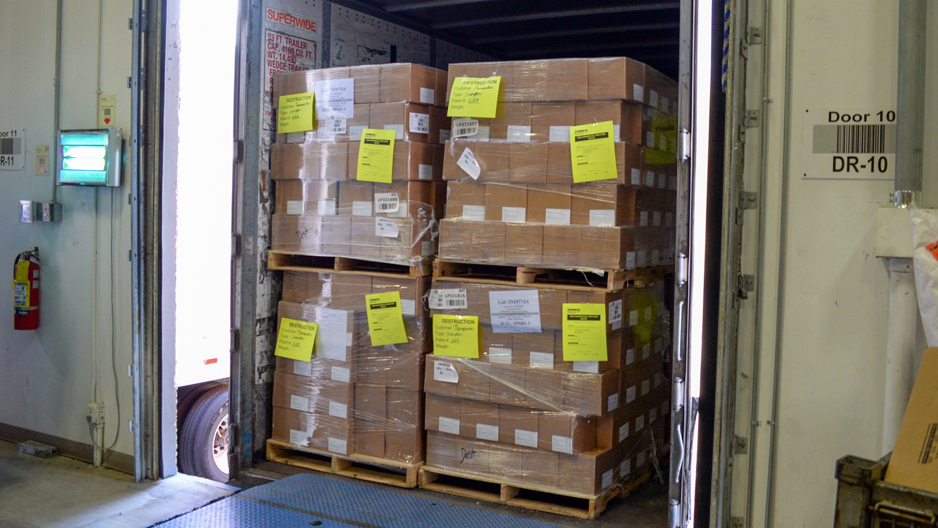 Pallets with expired product loaded onto trucks for transport to pharmaceutical destruction site.