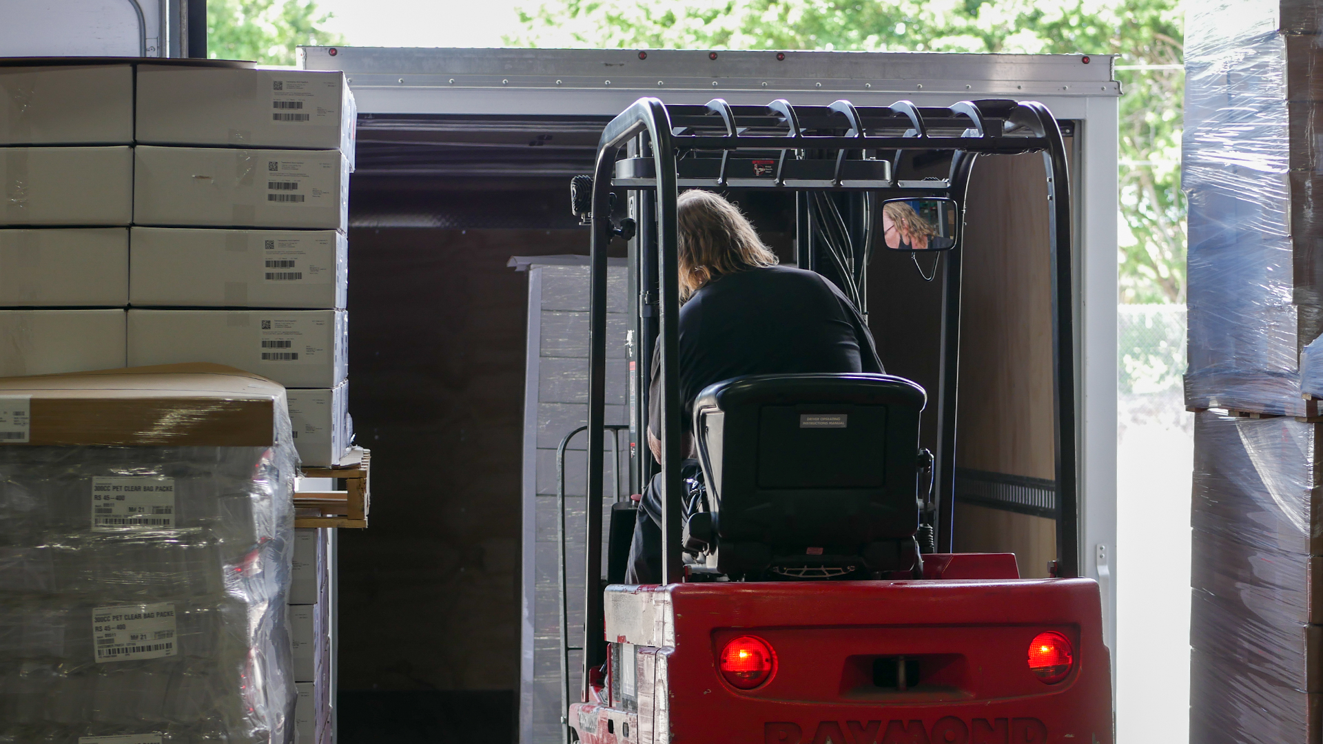 Warehouse Supervisor fills truck with pallets using forklift.