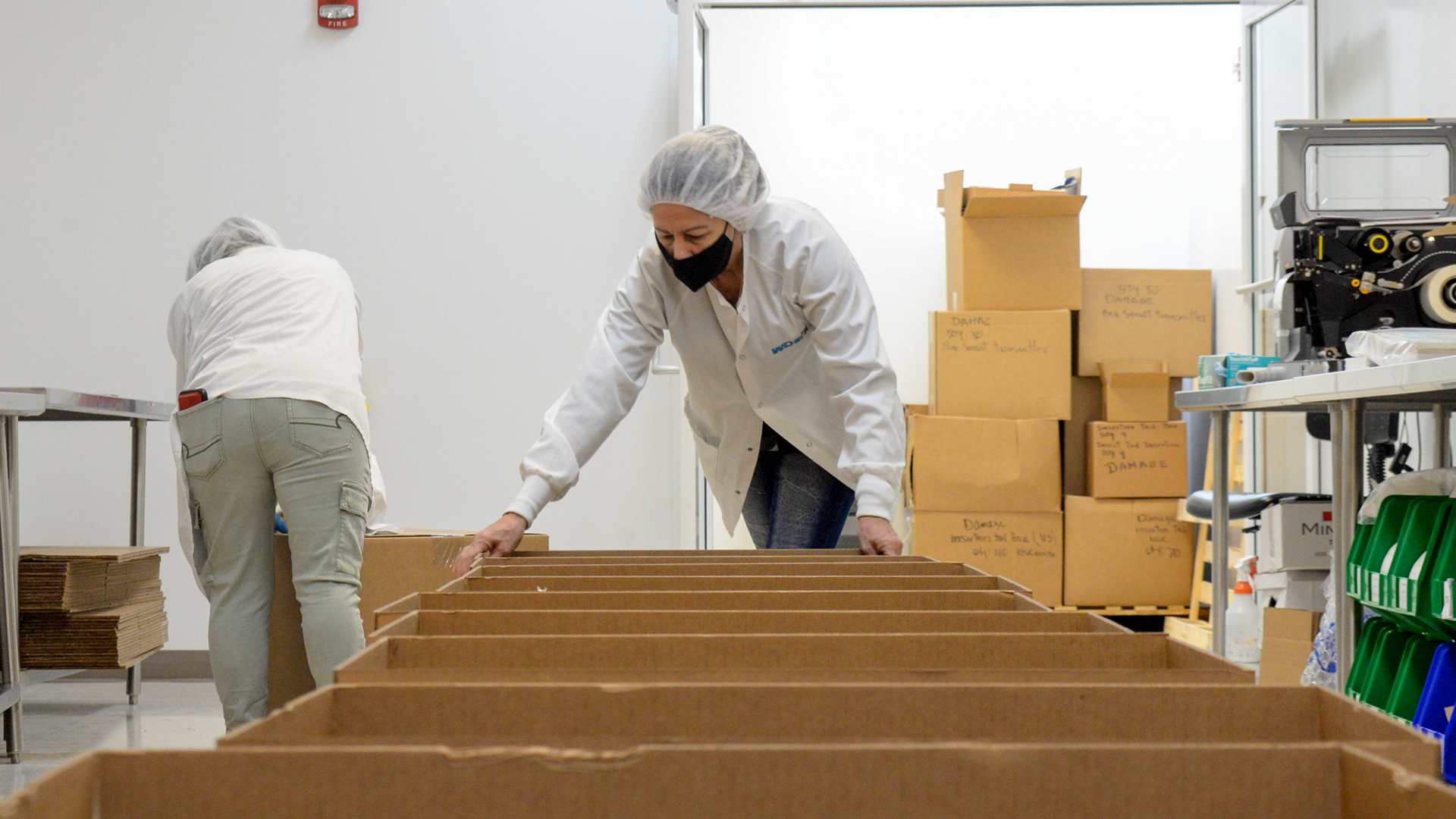 two production technicians preparing boxes for kitting project